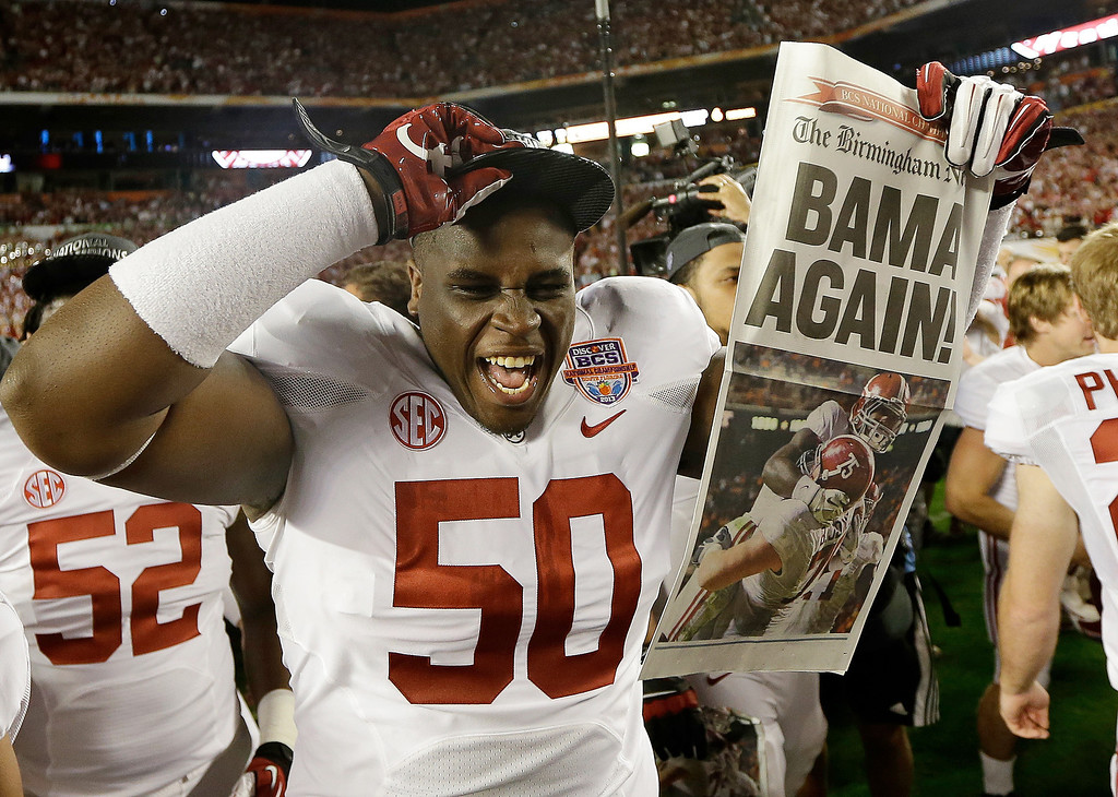 Description of . Alabama defensive lineman Alphonse Taylor (50) holds up a newspaper after the BCS National Championship college football game Monday, Jan. 7, 2013, in Miami. Alabama won 42-14. (AP Photo/David J. Phillip)