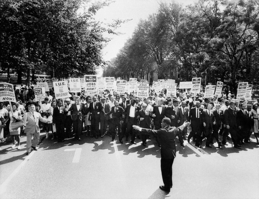 Description of . The clergyman and civil rights leader Martin Luther KIng (C) and other black and white civil right leaders march 28 August 1963 on the Mall in Washington DC during the