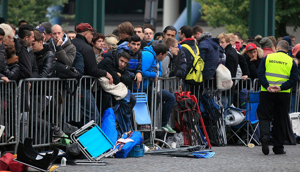 Description of . People queue outside an Apple store for the start of the new iPhone sale in Oberhausen, Germany, Friday, Sept. 20, 2013. (AP Photo/Frank Augstein)