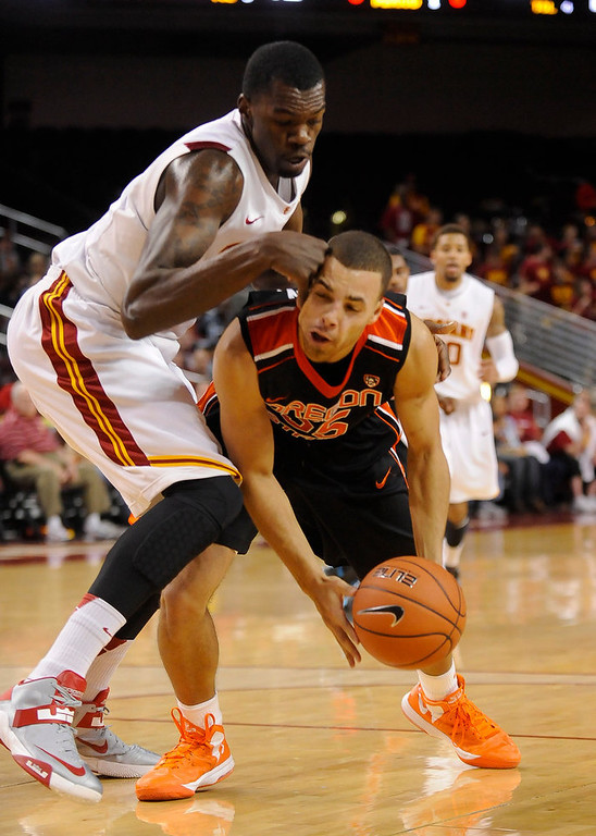 Description of . Southern Cal forward Dewayne Dedmon (14) collides with Oregon State guard Roberto Nelson, right, as he attempts to get by him during the first half of an NCAA college basketball game, Saturday, Jan. 19, 2013, in Los Angeles. (AP Photo/Gus Ruelas)