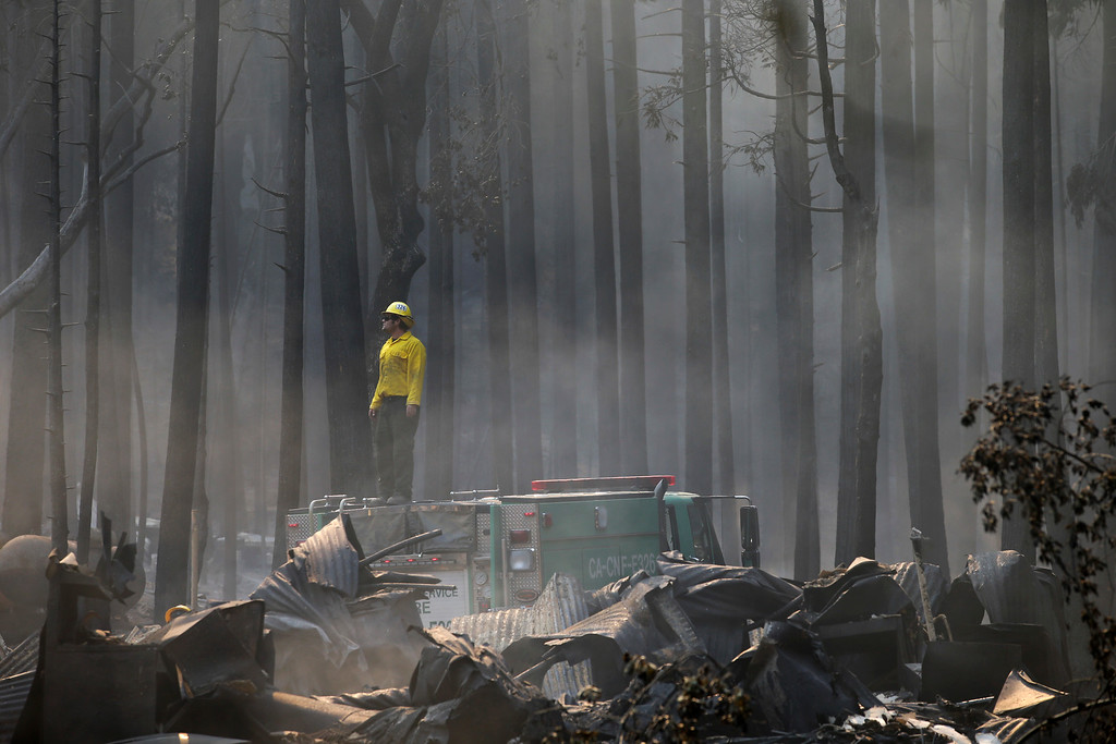 Description of . A firefighter stands on top of a fire truck at a campground destroyed by the Rim Fire near Yosemite National Park, Calif., on Monday, Aug. 26, 2013. Crews working to contain one of California's largest-ever wildfires gained some ground Monday against the flames threatening San Francisco's water supply, several towns near Yosemite National Park and historic giant sequoias. (AP Photo/Jae C. Hong)