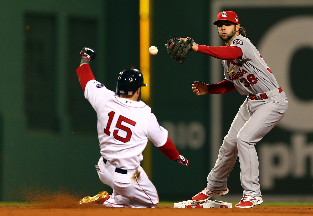 Description of . Pete Kozma #38 of the St. Louis Cardinals drops the ball as Dustin Pedroia #15 of the Boston Red Sox slides into second base during Game One of the 2013 World Series at Fenway Park on October 23, 2013 in Boston, Massachusetts.  (Photo by Elsa/Getty Images)