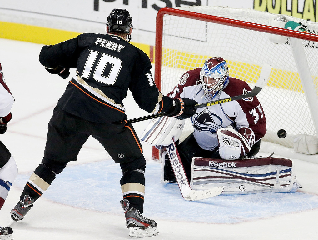 Description of . Anaheim Ducks right wing Corey Perry, left, scores the winning goal past Colorado Avalanche goalie Jean-Sebastien Giguere during overtime of an NHL hockey game in Anaheim, Calif. Sunday, Feb. 24, 2013. The Ducks won 4-3. (AP Photo/Chris Carlson)
