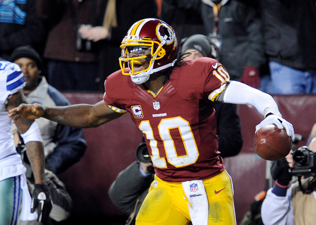 . Washington Redskins quarterback Robert Griffin III (10) celebrates his touchdown during the second half of an NFL football game against the Dallas Cowboys on Sunday, Dec. 30, 2012, in Landover, Md. (AP Photo/Nick Wass)