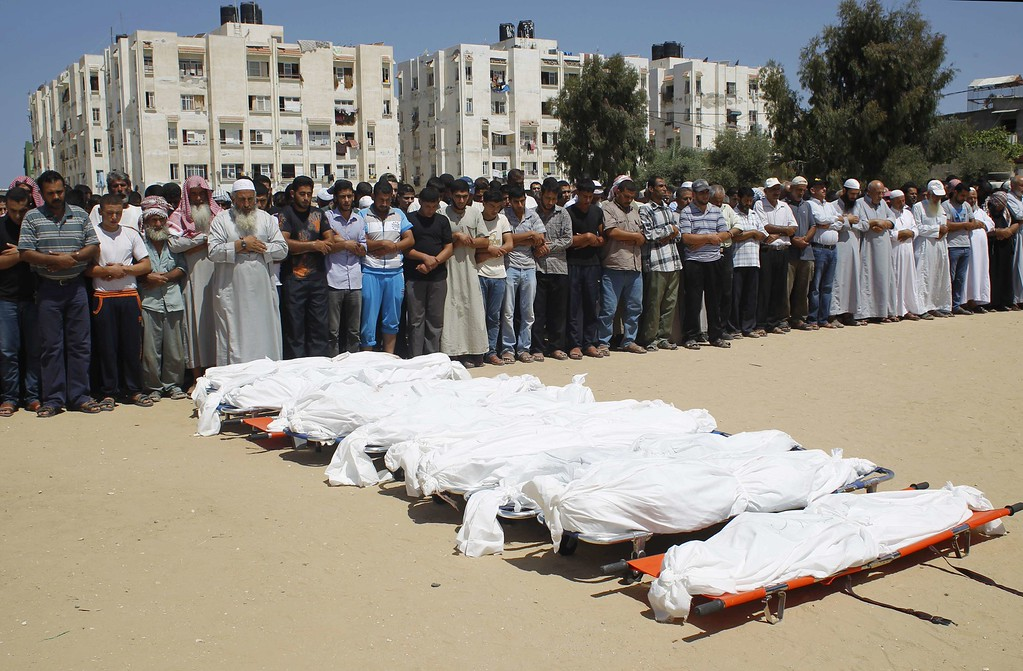Description of . Palestinian mourners pray in front of the bodies of ten members of the al-Astal family, that were killed in an Israeli air strike on their homes, during their funeral in Khan Yunis in the southern Gaza Strip on July 30, 2014. Israeli bombardments early on July 30 killed