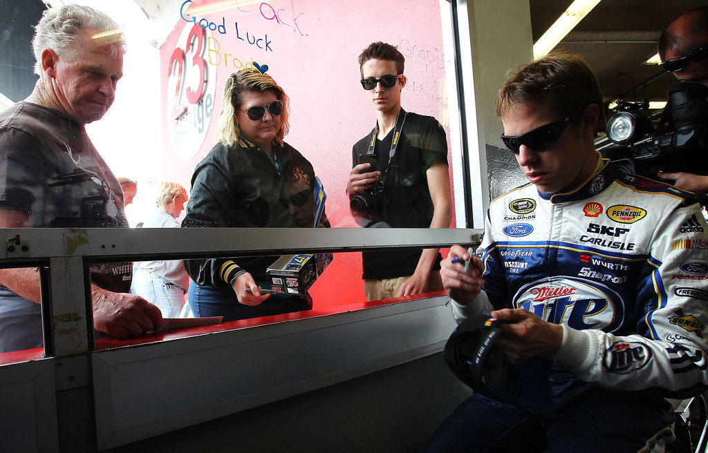 . DAYTONA BEACH, FL - FEBRUARY 20:  Brad Keselowski, driver of the #2 Miller Lite Ford, signs an autograph in the garage area during practice for the NASCAR Sprint Cup Series Daytona 500 at Daytona International Speedway on February 20, 2013 in Daytona Beach, Florida.  (Photo by Jonathan Ferrey/Getty Images)