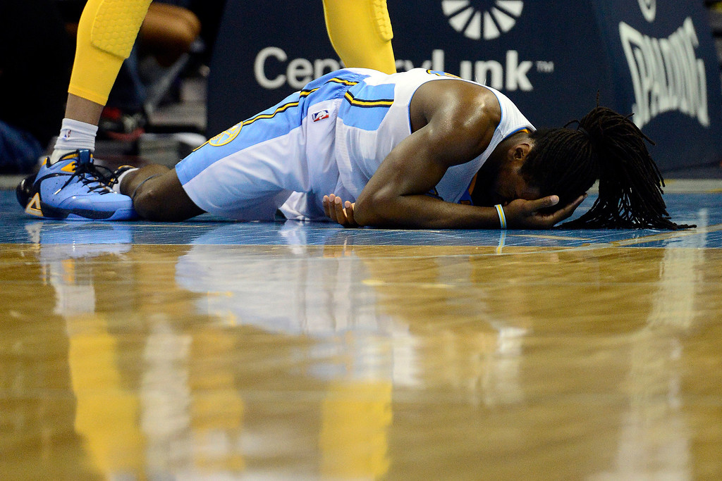 Description of . Denver Nuggets small forward Kenneth Faried (35) hits the deck after colliding with Los Angeles Lakers center Dwight Howard (12) during the second half of the Nuggets' 126-114 win at the Pepsi Center on Wednesday, December 26, 2012. Howard was ejected following the play. AAron Ontiveroz, The Denver Post