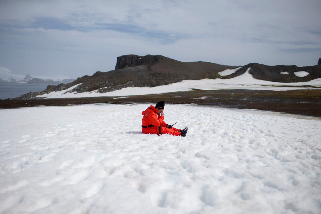 Description of . In this Jan. 24, 2015 photo, a worker from the Chile's Antarctic Institute sits on the snow on Robert Island, part of the South Shetland Islands archipelago in Antarctica. NASA uses the remoteness of Antarctic to study what people would have to go through if they visited Mars. The dry air also makes it perfect for astronomers to peer deep into space and into the past. (AP Photo/Natacha Pisarenko)
