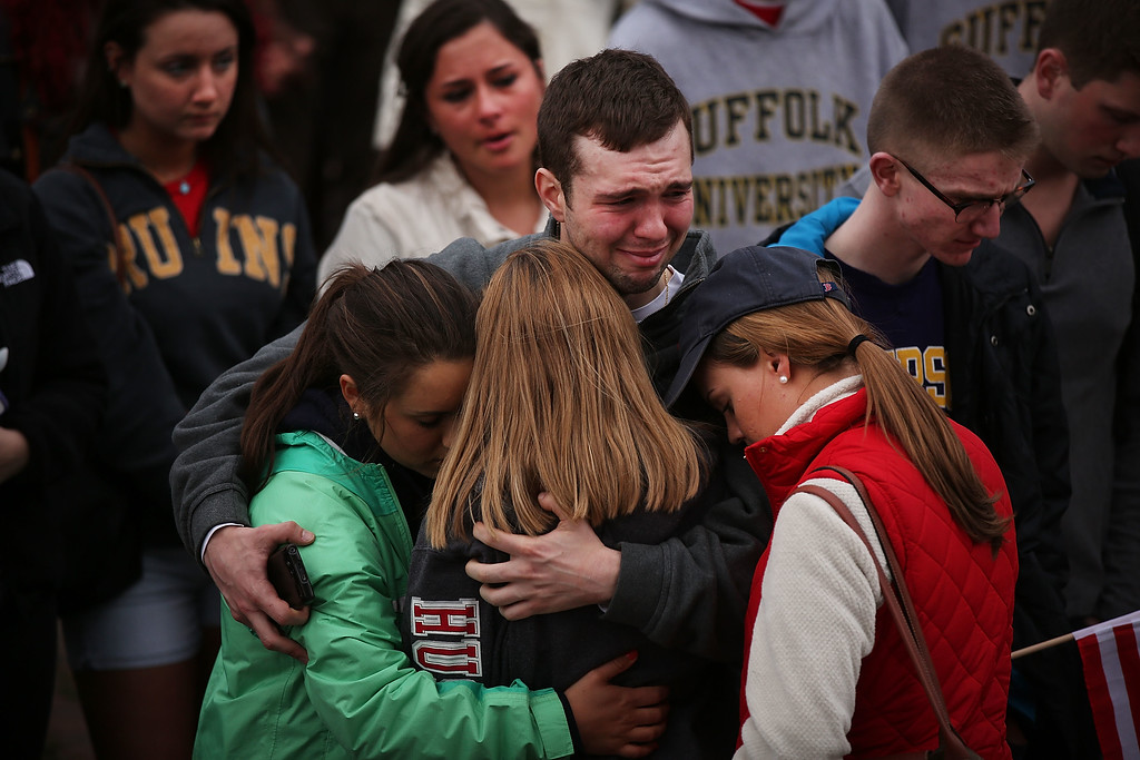 Description of . BOSTON, MA - APRIL 16: People hug and cry during a vigil for victims of the Boston Marathon bombings at Boston Commons on April 16, 2013 in Boston, Massachusetts. The twin bombings, which occurred near the marathon finish line, resulted in the deaths of three people while hospitalizing at least 140. The bombings at the 116-year-old Boston race, resulted in heightened security across the nation with cancellations of many professional sporting events as authorities search for a motive to the violence.  (Photo by Spencer Platt/Getty Images)