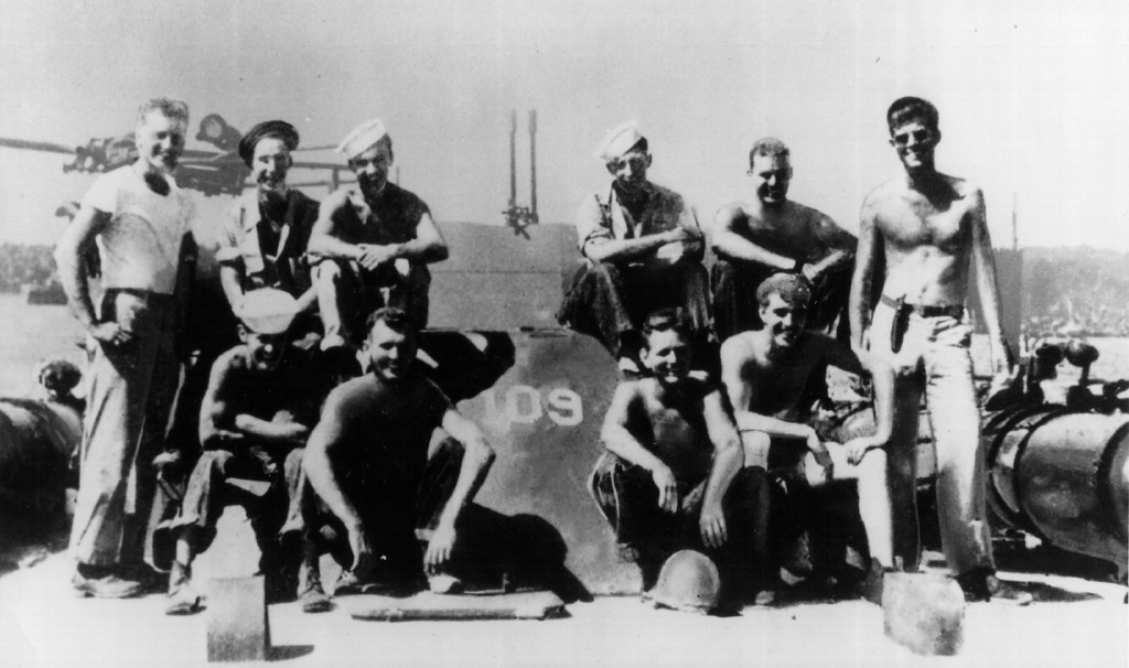 Description of . The future 35th president served as a U.S. Navy lieutenant and commander of a patrol torpedo (PT) boat during World War II. Kennedy is shown at the extreme right with members of his crew at a South Pacific naval base. National Archive/Newsmakers