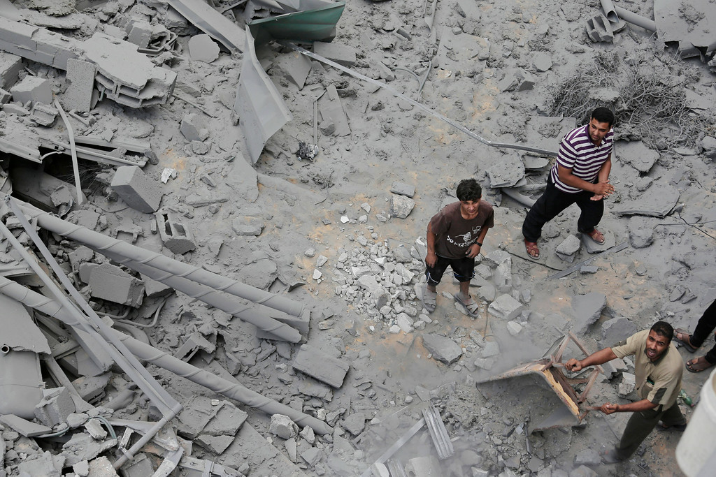 Description of . Palestinians from a neighboring apartment building carry out debris as they walk on the rubble of the offices of the Hamas movement's Al-Aqsa satellite TV station, in Gaza City, northern Gaza Strip, destroyed by an Israeli strike, Tuesday, July 29, 2014. Early Tuesday, Israel warplanes struck a series of targets in Gaza City, including the top Hamas leader in Gaza, Ismail Haniyeh's house and government offices, while Gaza's border area with Israel was hit by heavy tank shelling. (AP Photo/Lefteris Pitarakis)