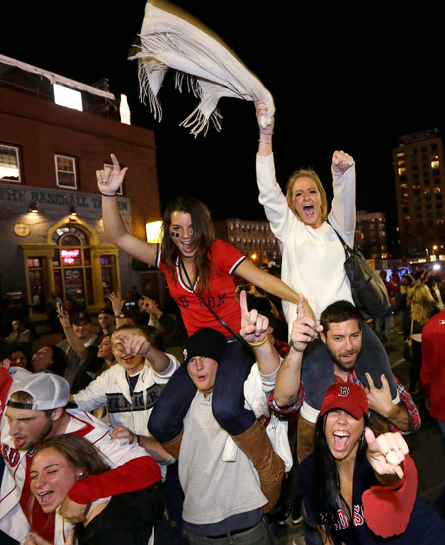 Description of . Boston Red Sox fans celebrate in the street near Fenway Park following Game 6 of baseball's World Series between the Red Sox and the St. Louis Cardinals on Wednesday, Oct. 30, 2013, in Boston. The Red Sox won 6-1 to win the series. (AP Photo/Steven Senne)