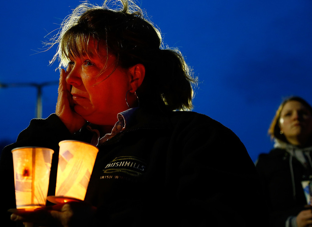 Description of . BOSTON, MA - APRIL 16: A woman cries while listening during the vigil for eight-year-old Martin Richard, from Dorchester, who was killed by an explosion near the finish line of the Boston Marathon on April 16, 2013 at Garvey Park in Boston, Massachusetts. The twin bombings resulted in the deaths of three people and hospitalized at least 128. The bombings at the 116-year-old Boston race resulted in heightened security across the nation with cancellations of many professional sporting events as authorities search for a motive to the violence. (Photo by Jared Wickerham/Getty Images)