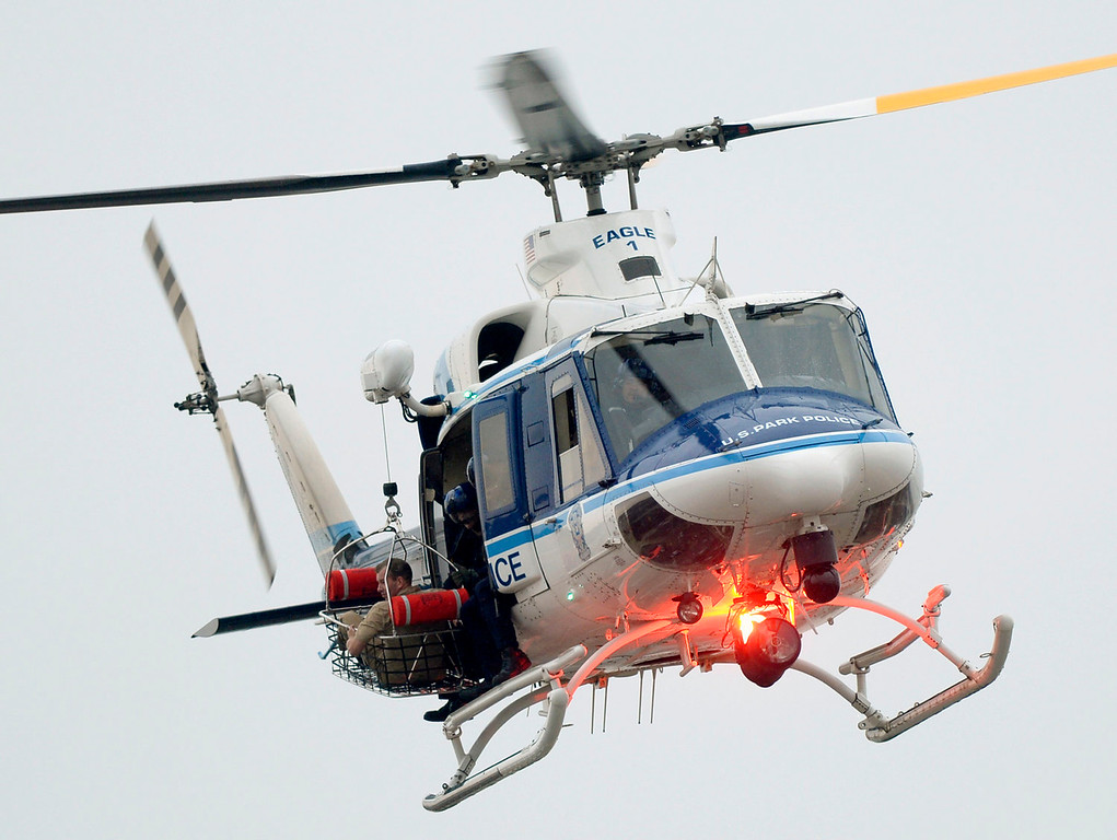 Description of . A U.S. Park Police helicopter with a person in the rescue basket, flies over a building at the Washington Navy Yard in Washington, Monday, Sept. 16, 2013. At least one gunman opened fire inside a building at the Washington Navy Yard on Monday morning. (AP Photo/Susan Walsh)