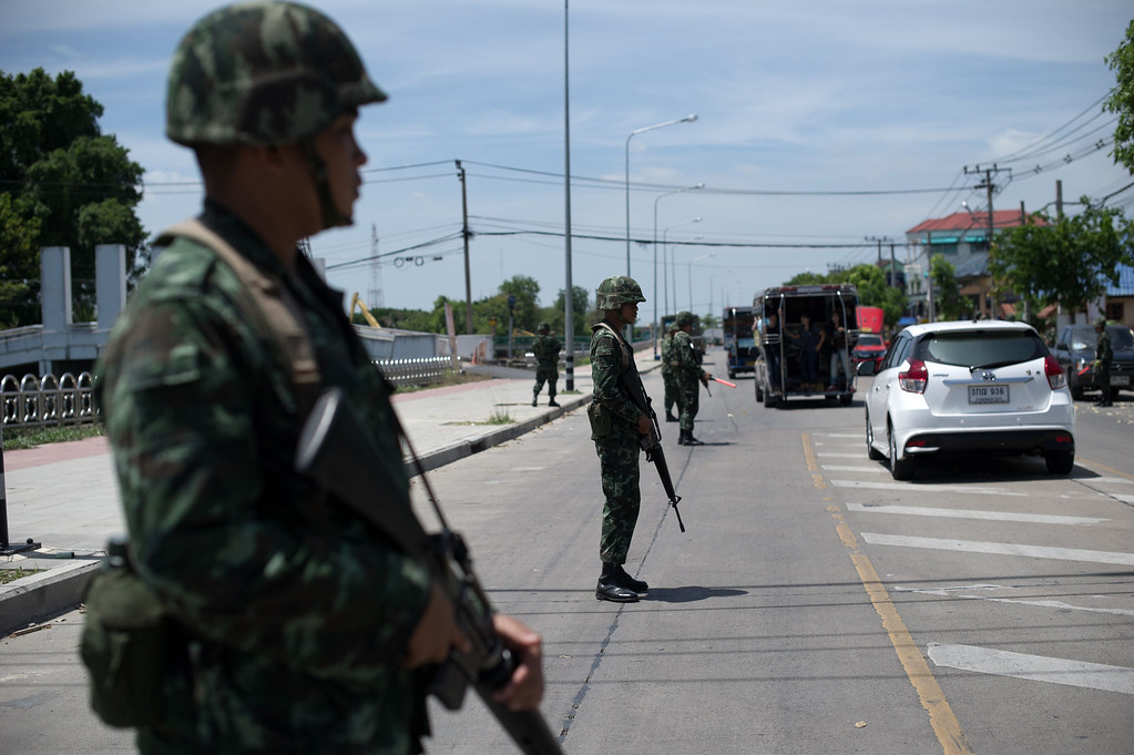 Description of . Thai army soldiers stand at a checkpoint near awhere pro-government \'\'Red shirts\'\' have been rallying for days on the outskirts of Bangkok on May 20, 2014. AFP PHOTO/ Nicolas ASFOURI/AFP/Getty Images