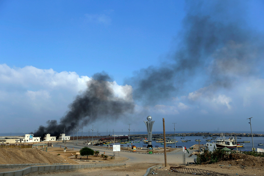 Description of . Smoke rises at the port in Gaza City, northern Gaza Strip, hit by an Israeli strike, Tuesday, July 29, 2014. According to Palestinians, the storage area at the port where the fishermen keep their nets and equipment was hit. Early Tuesday, Israel warplanes struck a series of targets in Gaza City, including Hamas leader Ismael Haniyeh's house and government offices, while Gaza's border area with Israel was hit by heavy tank shelling. (AP Photo/Lefteris Pitarakis)
