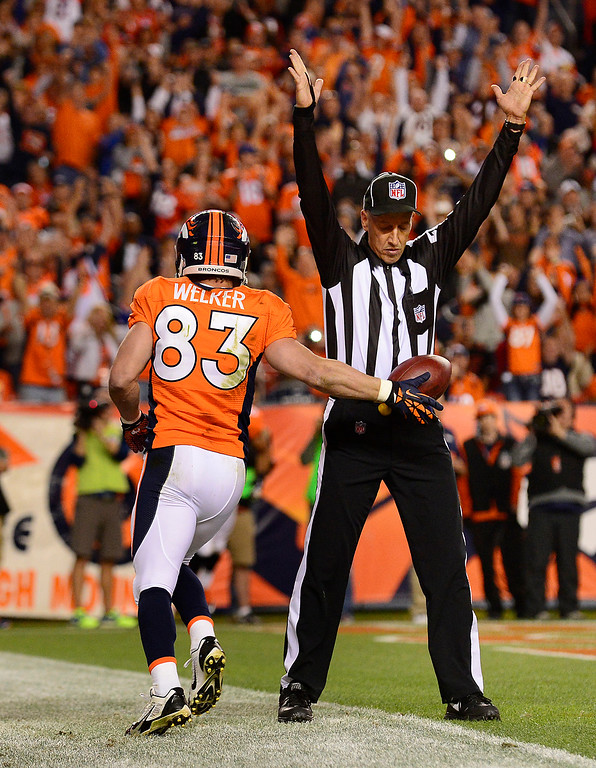 Description of . Denver Broncos wide receiver Wes Welker (83) hands the ball to the referee after scoring a touchdown in the second quarter. The Denver Broncos took on the Oakland Raiders at Sports Authority Field at Mile High in Denver on September 23, 2013. (Photo by AAron Ontiveroz/The Denver Post)