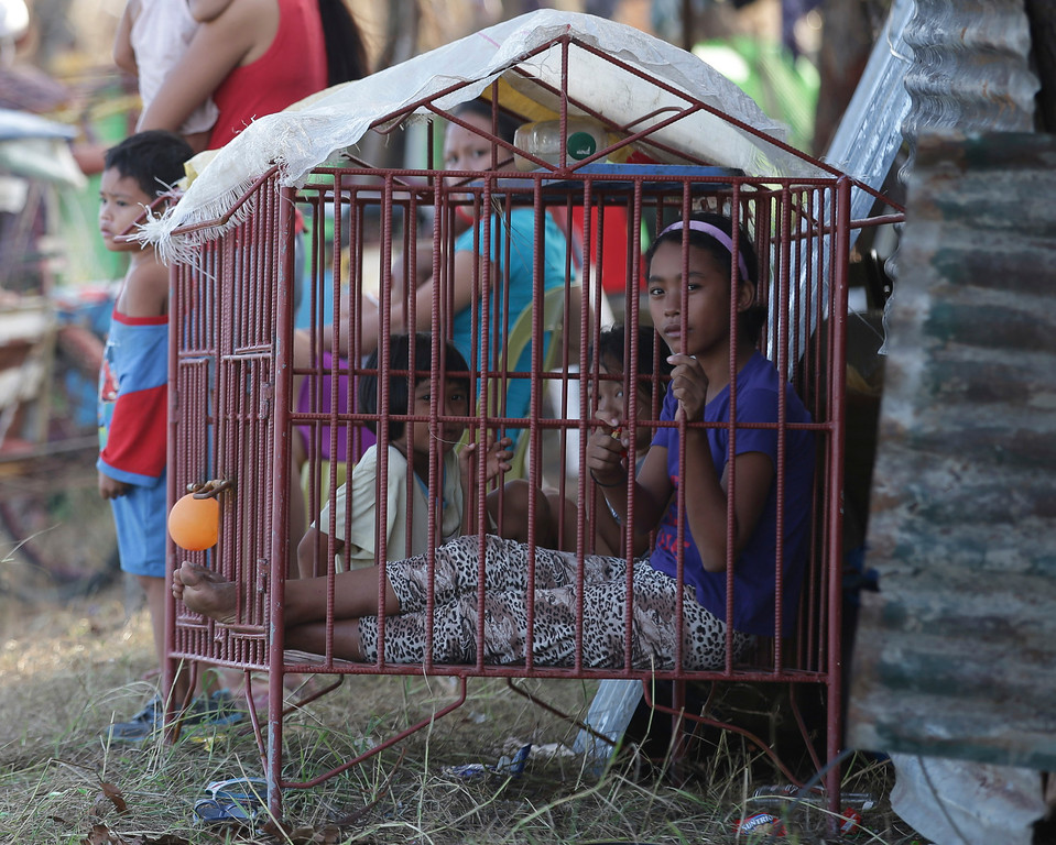 Description of . Despite living in the massive typhoon aftermath, young girls get to play in a dog house in Tacloban, central Philippines, Friday, Nov. 15, 2013.  (AP Photo/Aaron Favila)