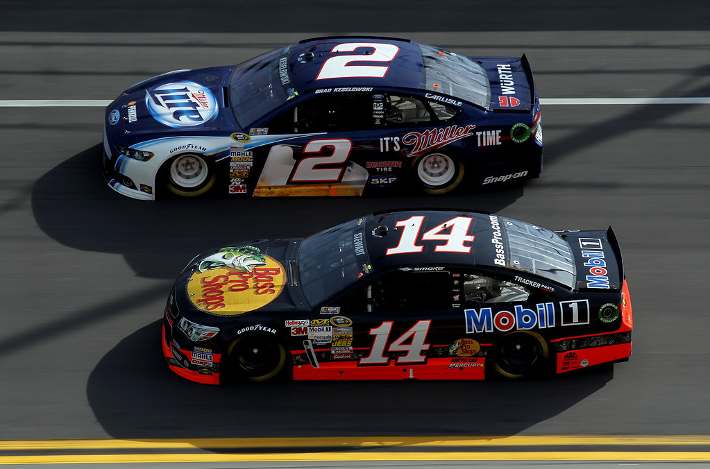 Description of . Tony Stewart, driver of the #14 Bass Pro Shops/Mobil 1 Chevrolet, and Brad Keselowski, driver of the #2 Miller Lite Ford, race side by side during the NASCAR Sprint Cup Series Budweiser Duel 1 at Daytona International Speedway on February 21, 2013 in Daytona Beach, Florida.  (Photo by Todd Warshaw/Getty Images)