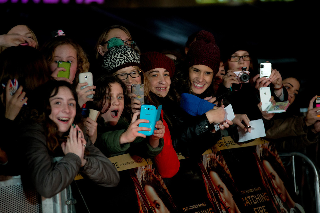 Description of . Fans watch the cast members arrive on the red carpet for the World Premiere of Hunger Games: Catching Fire, at a central London cinema, Monday, Nov. 11, 2013. (Photo by Joel Ryan/Invision/AP)