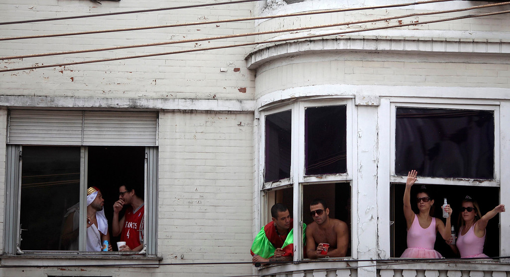 Description of . Revelers stand at windows as they observe the annual block party known as the