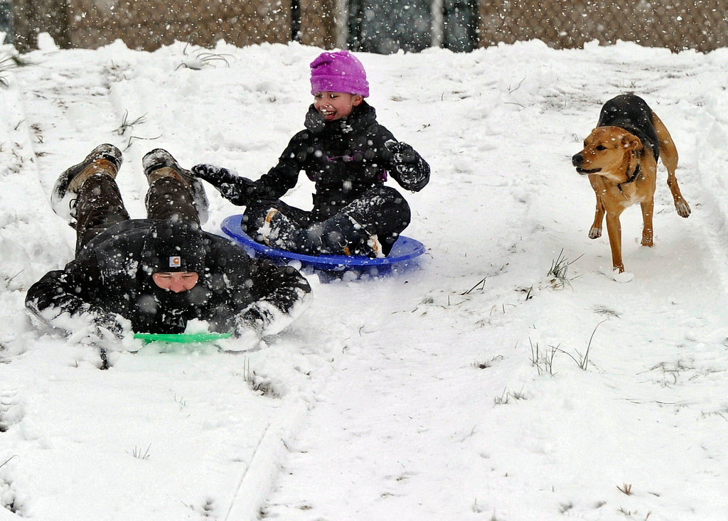 Description of . Jason Randall, along with daughter Hallie, and family dog Sandy sled down a hill in southern Greenville County during a snow storm set Wednesday, Feb. 12, 2014, near Greenville, S.C.(AP Photo/ Richard Shiro)