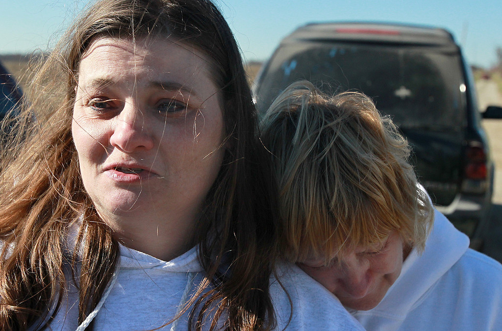Description of . Amy Tippin is comforted while talking about running to a nearby creek to escape the tornado with her two sons while fleeing from her mobile home (which was destroyed) Sunday, Nov. 17, 2013, when the storm hit. Tippin lives on the property a few feet from the destroyed home of her deceased grandmother Frances Hoy and great uncle Joesph Hoy. (AP Photo/ Belleville News-Democrat,Steve Nagy)