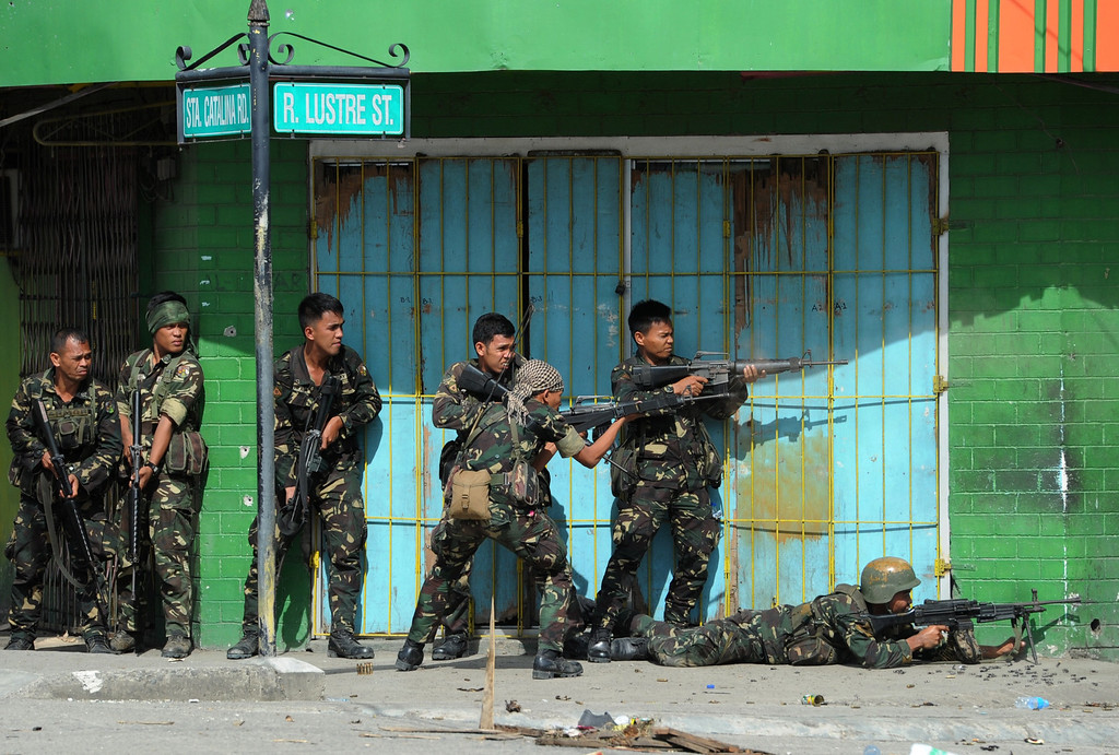 Description of . Philippine soldiers fire towards enemy position during a fire fight between government forces and Muslim rebels as stand-off entered its fourth day in Zamboanga City on the southern island of Mindanao on September 12, 2013.   AFP PHOTO/TED ALJIBE/AFP/Getty Images
