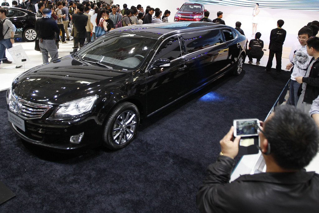 Description of . Visitors watch a Changan Reaton car at the China International Exhibition Center new venue during the