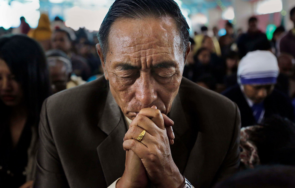 Description of . A Christian man prays during Christmas mass in a church in Gauhati, India, Wednesday, Dec. 25, 2013. Although Christians comprise only two percent of the population among a Hindu majority, the holiday is observed across the country as an occasion to celebrate. (AP Photo/Anupam Nath)