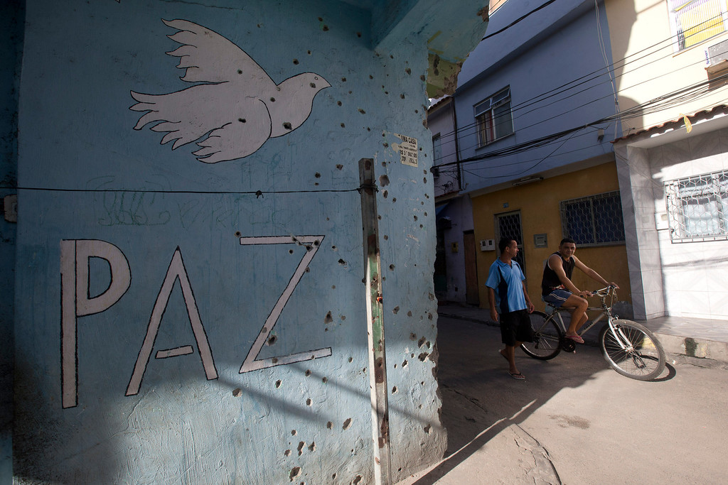 ". Two men walk beside a sign that reads ""Peace\"" on a wall covered with holes from bullets of past shootings, during an operation to occupy the Mare slum complex in Rio de Janeiro, Brazil, Saturday, April 5, 2014. More than 2,000 Brazilian Army soldiers moved into the Mare slum complex early Saturday in a bid to improve security and drive out the heavily armed drug gangs that have ruled the sprawling slum for decades. (AP Photo/Silvia Izquierdo)"