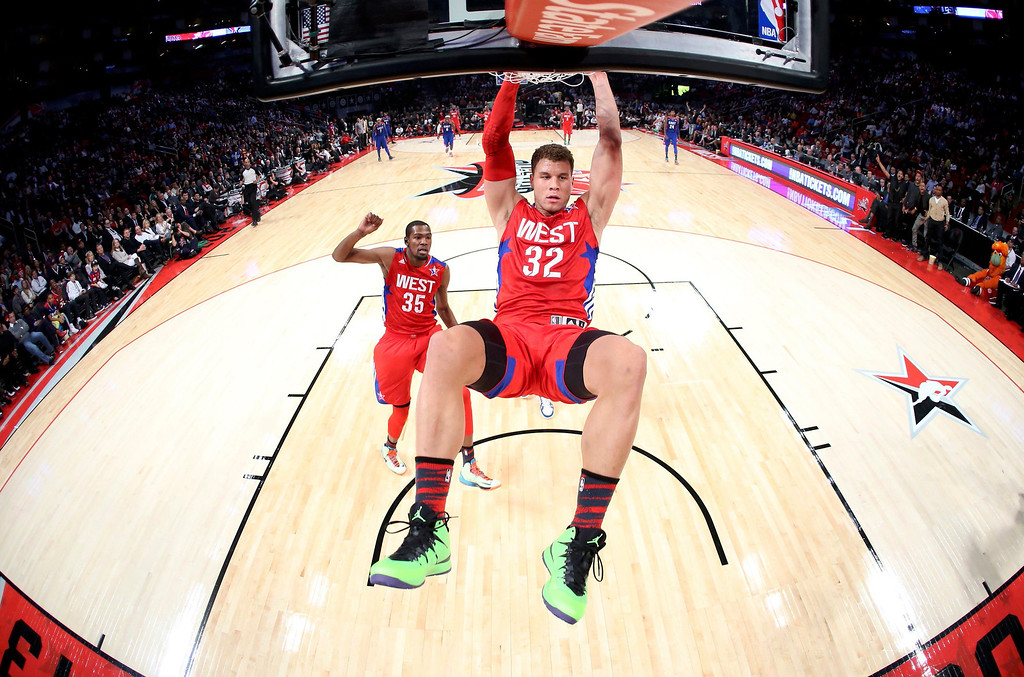 Description of . NBA All-Star Blake Griffin of the Los Angeles Clippers (C) hangs onto the rim after dunking during the 2013 NBA All-Star basketball game in Houston, Texas, February 17, 2013. REUTERS/Ronald Martinez-POOL
