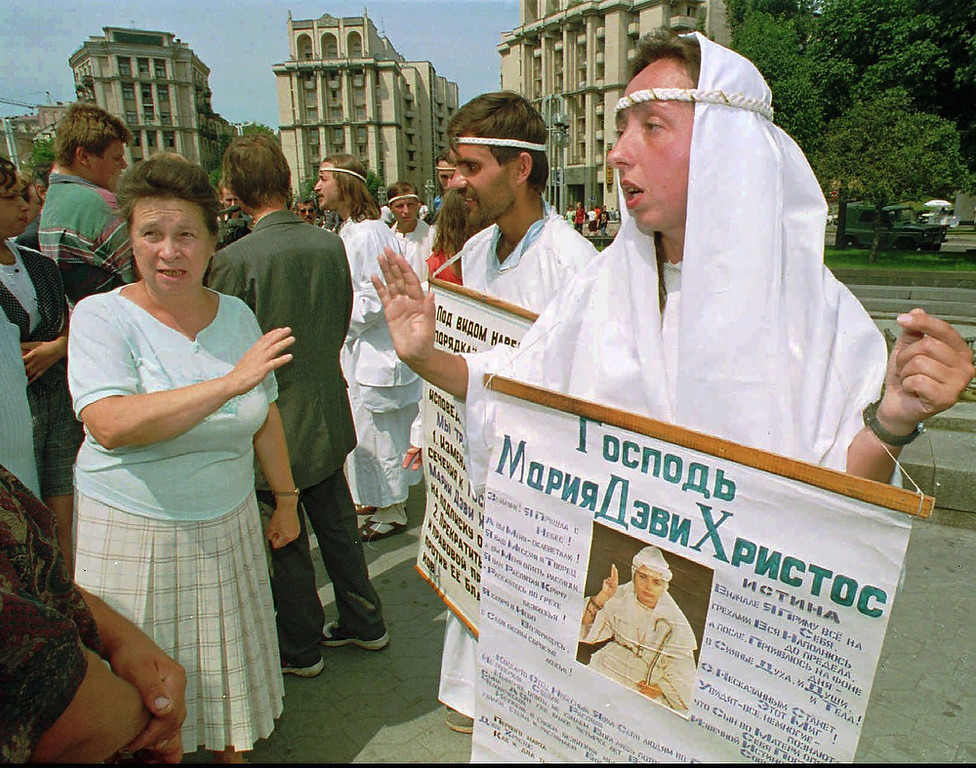 Description of . About 10 members of the religious White Brotherhood sect, referred to as The Doomsday Cult, are dressed in white robes as they gather in central Kiev, Ukraine, Monday July 24, 1995 and hold posters with the portrait of their leader. Activity of this religious sect was prohibited in Nov, 1993 when their leader Maria Devi Christos and cult members were arrested for inciting mass disorder. The group's