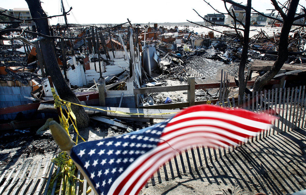 . Flags decorate a fence Thursday, April 25, 2013, in Brick, N.J., around the burned remains of more than 60 small bungalows at Camp Osborn which were destroyed last October during Superstorm Sandy. Six months after Sandy devastated the Jersey shore and New York City and pounded coastal areas of New England, the region is dealing with a slow and frustrating recovery. (AP Photo/Mel Evans)