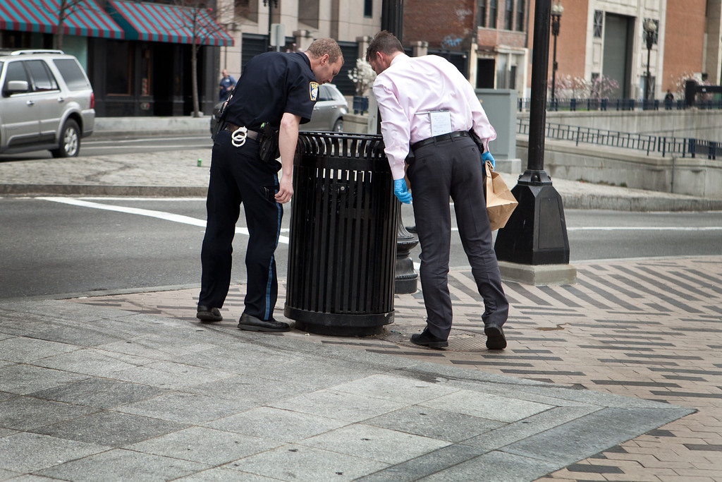 Description of . A Boston Police officer and detective search South Station for suspicious material after two bullets were found outside of the T stop on April 19, 2013 in Boston, Massachusetts. (Photo by Kayana Szymczak/Getty Images)
