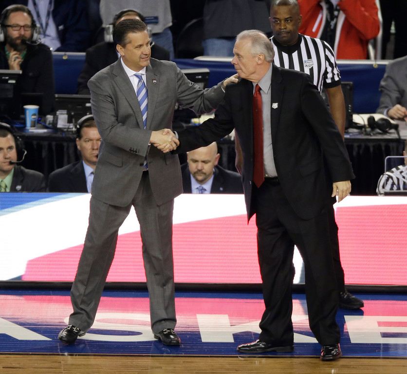 Description of . Kentucky head coach John Calipari, left, greets Wisconsin head coach Bo Ryan before an NCAA Final Four tournament college basketball semifinal game Saturday, April 5, 2014, in Arlington, Texas.(AP Photo/Tony Gutierrez)