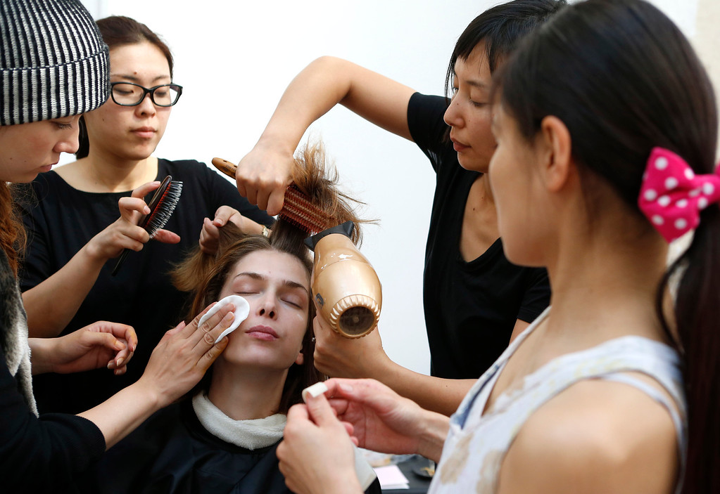 Description of . A model is made up backstage before the presentation of Ground Zero's ready-to-wear Spring/Summer 2014 fashion collection, in Paris, Tuesday, Sept.24, 2013. (AP Photo/Jacques Brinon)