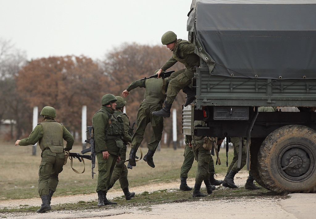 Description of . LUBIMOVKA, UKRAINE - MARCH 04:  Troops under Russian command jump down from a truck with orders to shoot to kill anyone who advances further after over 100 unarmed Ukrainian troops confronted them at the Belbek airbase, which the Russian troops are occcupying, in Crimea on March 4, 2014 in Lubimovka, Ukraine. The Ukrainians are stationed at their garrison nearby, and after spending a tense night anticipating a Russian attack following the expiration of a Russian deadline to surrender, in which family members of troops spent the night at the garrison gate in support of the soldiers, their commander Colonel Yuli Mamchor announced his bold plan this morning to retake the airfield by confronting the Russian-lead soldiers unarmed. The Russian-lead troops fired their weapons into the air but then granted Mamchor the beginning of negotiations with their commander. Russian-lead troops have blockaded a number of Ukrainian military bases across Crimea.  (Photo by Sean Gallup/Getty Images)
