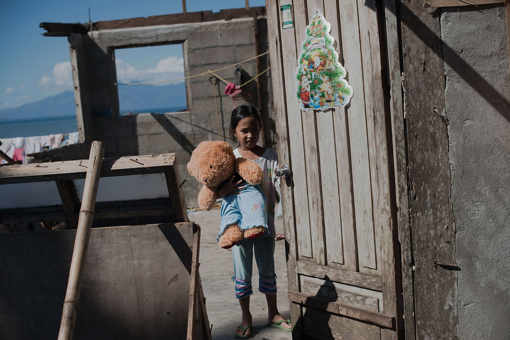 Description of . A typhoon victim holds her teddy bear at her destroyed house in Copoocan on November 18, 2013. The United Nations has confirmed at least 4,500 killed in the disaster, which brought five-meter (16-foot) waves to Tacloban, flattening nearly everything in their path as they swept hundreds of meters across the low-lying land. NICOLAS ASFOURI/AFP/Getty Images