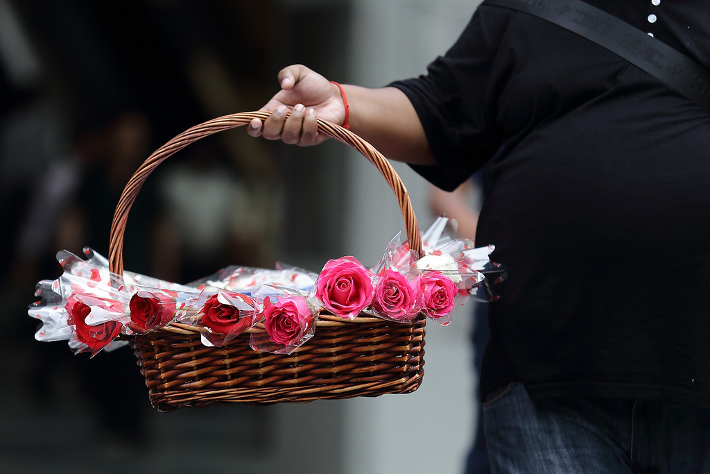 Description of . A man sells flowers during Valentine's Day at Raffles Place on 14 February, 2013 in Singapore.  Valentine's Day is a time to celebrate love, romance and friendship and is celebrated worldwide annually in different ways on February 14. (Photo by Suhaimi Abdullah/Getty Images)