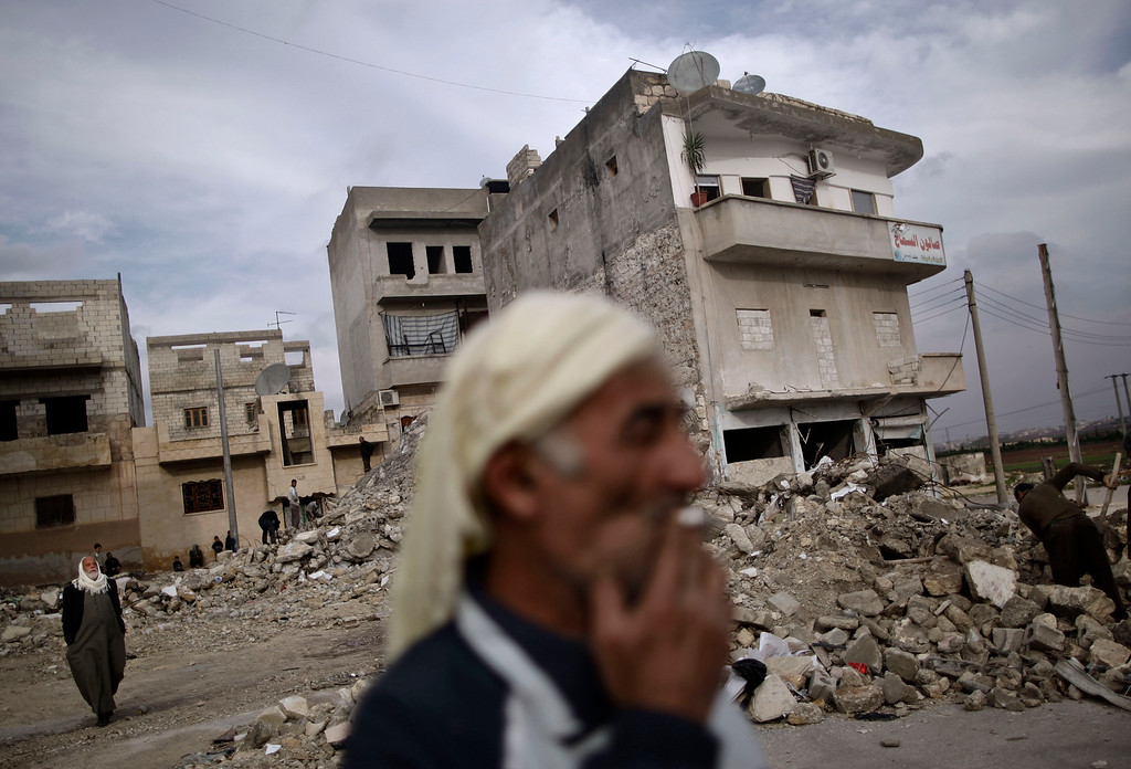 Description of . In this Wednesday, Dec. 12, 2012 file photo, an elderly Syrian man smokes a cigarette as he stands next to a residential building destroyed in a government airstrike, in Maaret Misreen, near Idlib, Syria. A U.S.-based rights group on Thursday accused Syria of war crimes by indiscriminate and sometimes deliberate airstrikes against civilians, killing at least 4,300 people since last summer. (AP Photo/Muhammed Muheisen)