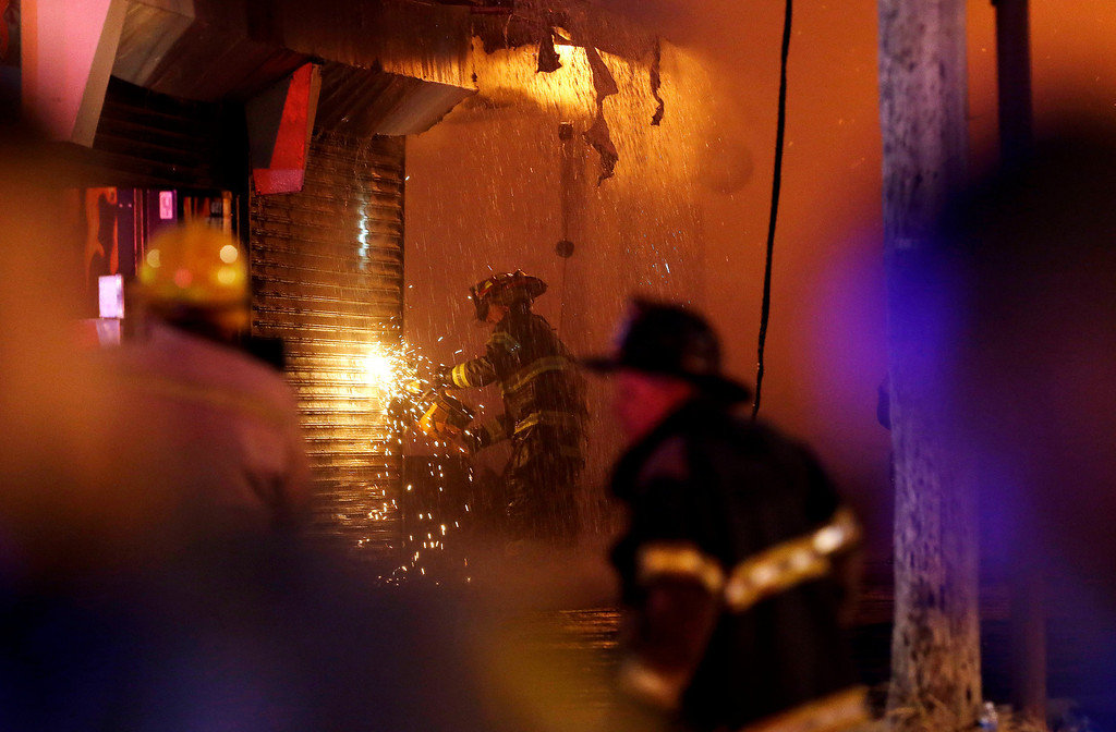 Description of . A firefighter saws through a metal wall on a building while battling a fire at the Seaside Park boardwalk on Thursday, Sept. 12, 2013, in Seaside Park, N.J. The fire began in a frozen custard stand on the Seaside Park section of the boardwalk and quickly spread north into neighboring Seaside Heights. (AP Photo/Julio Cortez)