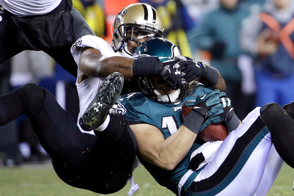 Description of . Philadelphia Eagles' Riley Cooper, right, is tackled by New Orleans Saints' Rafael Bush during the first half of an NFL wild-card playoff football game, Saturday, Jan. 4, 2014, in Philadelphia. (AP Photo/Matt Rourke)