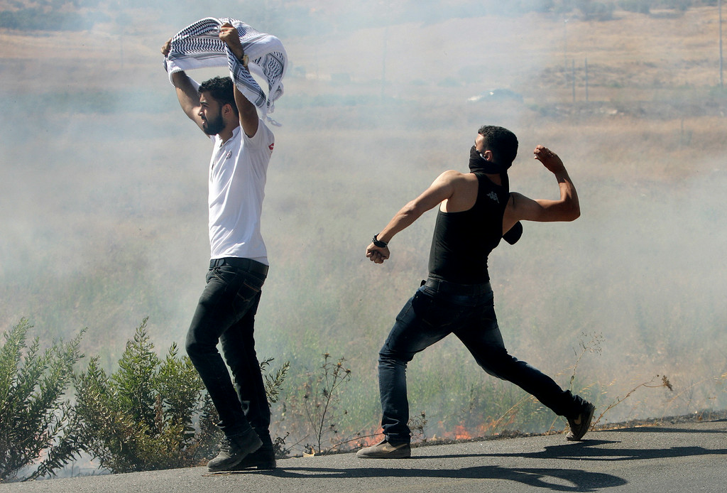 Description of . Palestinian protesters hurl stones at Israeli soldiers during a demonstration against the Israeli military action in Gaza, near the West Bank town of Nablus, Wednesday, July 16, 2014. Hundreds of Palestinian families, their children crying, fled Wednesday, as Israel intensified airstrikes on Hamas targets, including homes of the movement's leaders, following failed Egyptian cease-fire efforts. Before the renewed bombardment, Israel had told tens of thousands of residents of border areas to evacuate their neighborhoods. (AP Photo/Nasser Ishtayeh)
