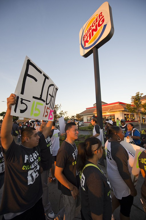 Description of . Fast food workers and their supporters picket outside a Burger King restaurant in Los Angeles on August 29, 2013. Fast food workers walked off their jobs as part of a nationwide strike demanding higher wages and the right to form a union.     AFP PHOTO / Robyn BECK/AFP/Getty Images