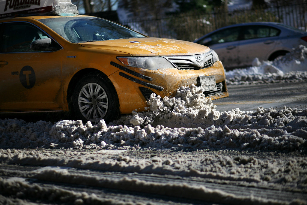 Description of . A taxi cab drives into a pile of snow on East End Ave. near E. 86th St. after an overnight storm dropped up to 7 inches of snow on January 04, 2014 in New York City. The Northeast and Midwest regions of the United States were hit with a large amount of snowfall accompanied by blizzard-like winds and plummeting temperatures this week. (Photo by Yana Paskova/Getty Images)