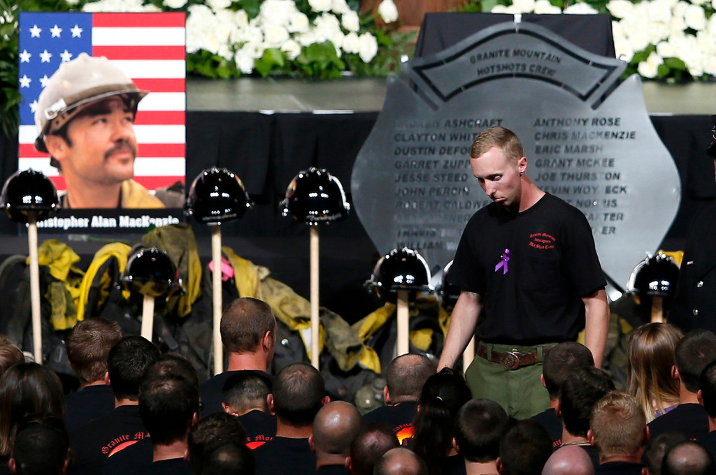 Description of . Surviving Hotshot crew member Brendan McDonough walks back to his seat after speaking at a memorial service for the fallen members of the Granite Mountain Hotshots, in Prescott Valley, Arizona July 9, 2013.   REUTERS/Lucy Nicholson