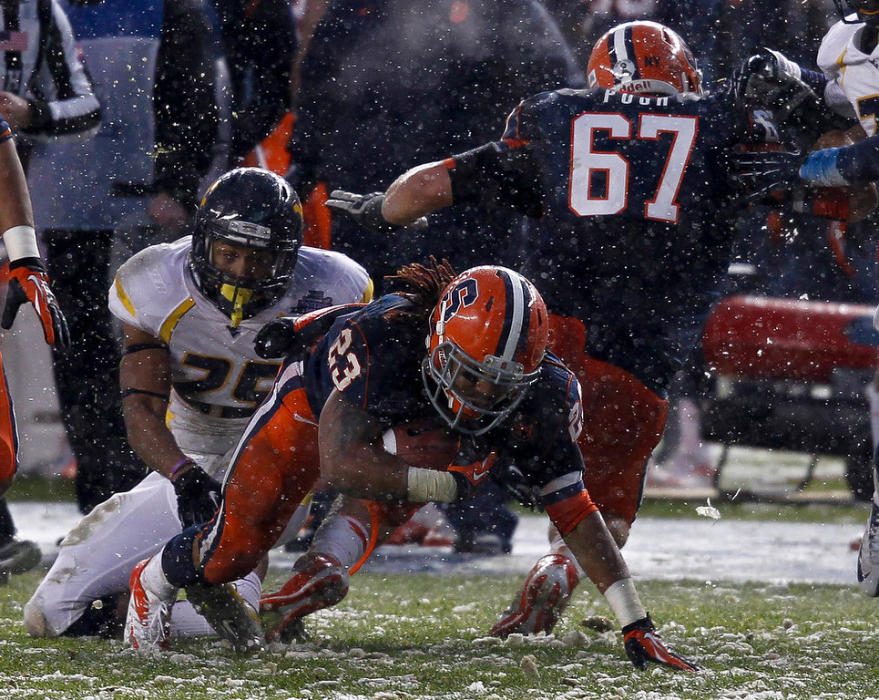 Description of . Prince-Tyson Gulley #23 of the Syracuse Orange scrambles away from Darwin Cook #25 of the West Virginia Mountaineers in the New Era Pinstripe Bowl at Yankee Stadium on December 29, 2012 in the Bronx borough of New York City.  (Photo by Jeff Zelevansky/Getty Images)