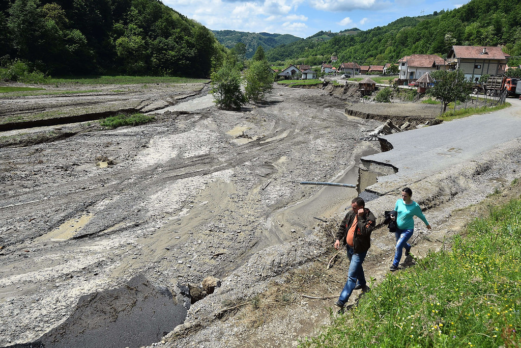 Description of . People walk along a collapsed road damaged by flooding  in Krupanj, some 130 kilometers south west of Belgrade, on May 20, 2014, after the western Serbian town was hit with floods and landslides, cutting it off for four days. Serbia declared three days of national mourning on May 20 as the death toll from the worst flood to hit the Balkans in living memory rose and health officials warned of a possible epidemic.    AFP PHOTO / ANDREJ  ISAKOVIC/AFP/Getty Images