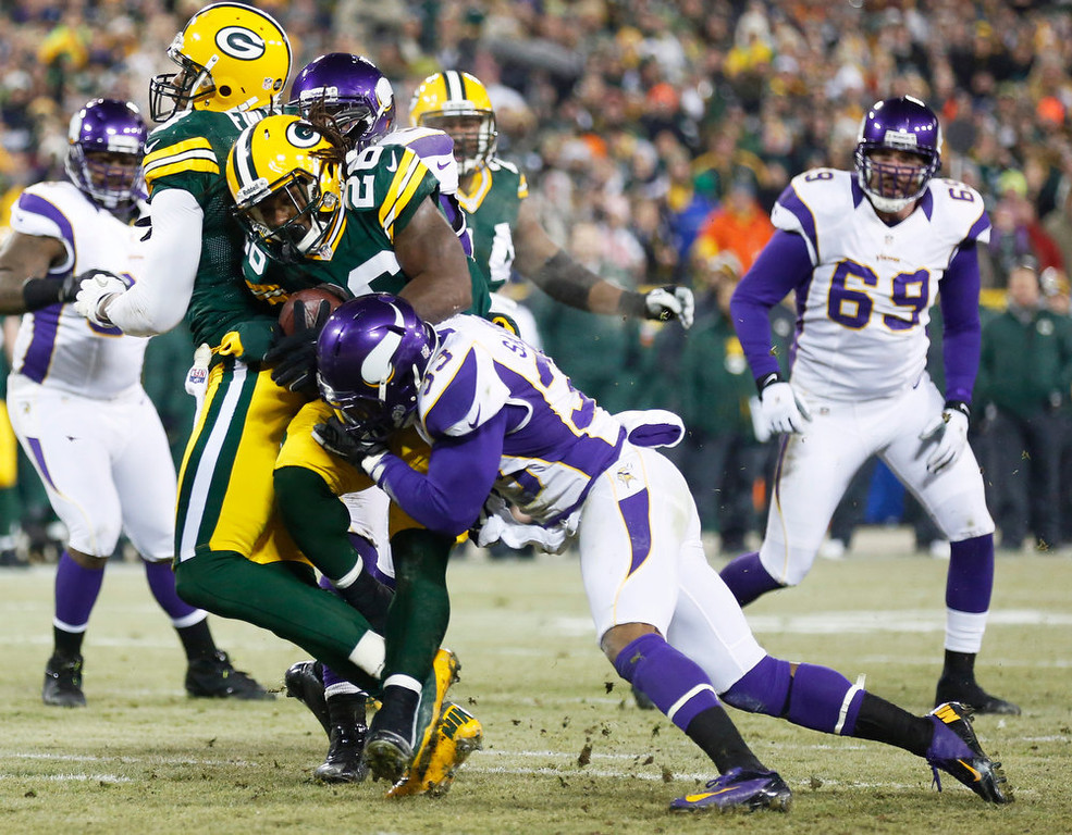 Description of . Green Bay Packers running back DuJuan Harris (26) tries to break a tackle by Minnesota Vikings strong safety Jamarca Sanford (33) during a touchdown run in the first half of an NFL wild card playoff football game Saturday, Jan. 5, 2013, in Green Bay, Wis. (AP Photo/Jeffrey Phelps)